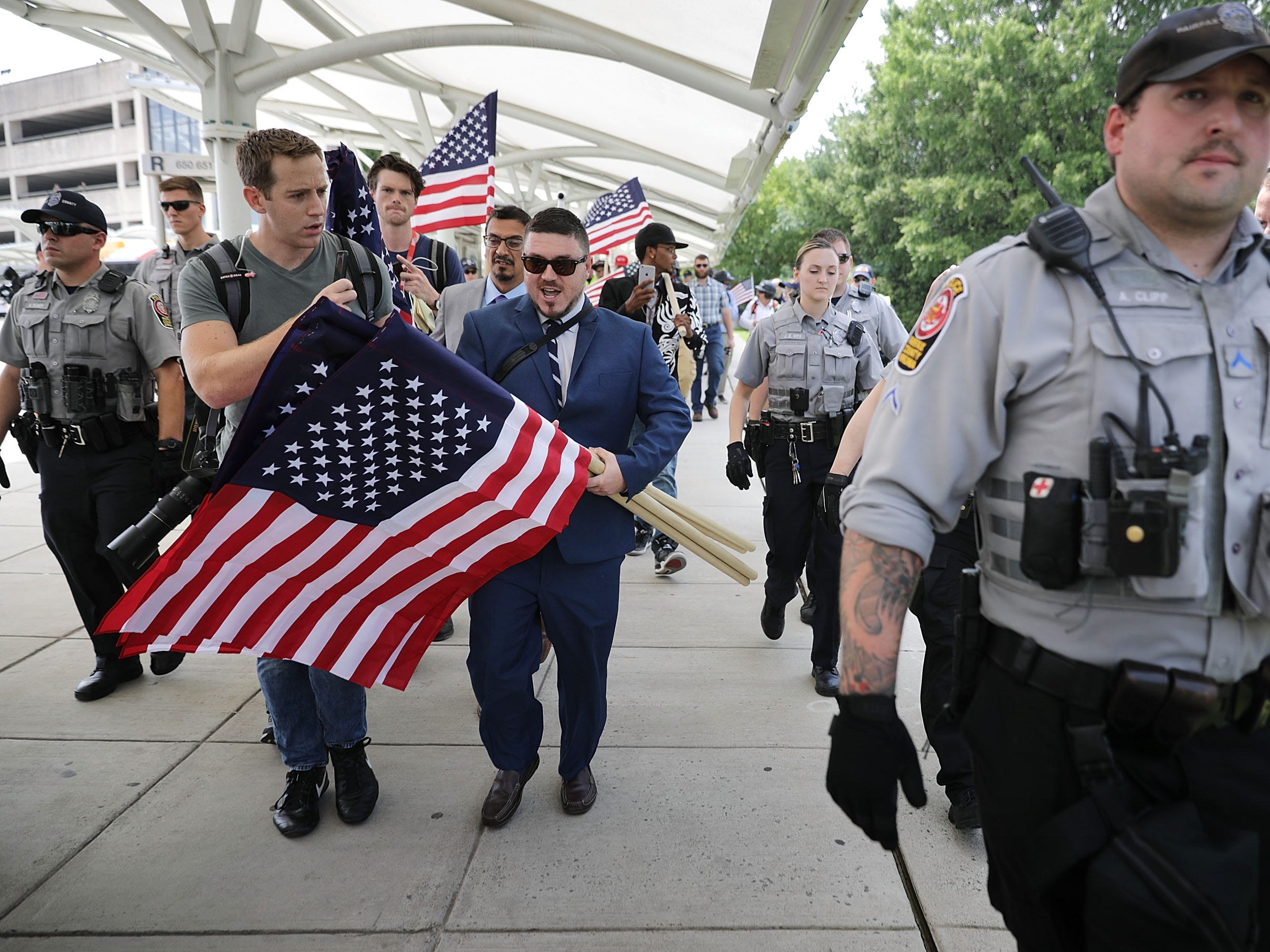 "Surrounded by his supporters, reporters and Fairfax County Police, Jason Kessler, center,  walks toward the Vienna/Fairfax  GMU Metro Station to travel by train to the White House for his white supremacist ""Unite the Right"" rally Aug. 12, 2018 in Vienna, Va. Thousands of protesters are expected to demonstrate against the ""white civil rights"" rally in Washington, which was planned by the organizer of last year's deadly rally in Charlottesville, Va."