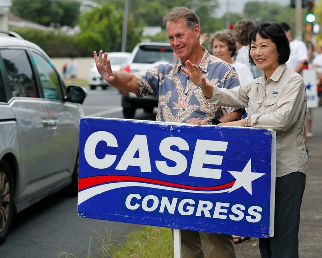 Former U.S. Rep Ed Case, left, along with his wife Audrey Case, do last minute campaigning waving at passing cars, Saturday, Aug. 11, 2018, in Honolulu. Case is trying to succeed U.S. Rep Colleen Hanabusa, who is running for Hawaii governor.