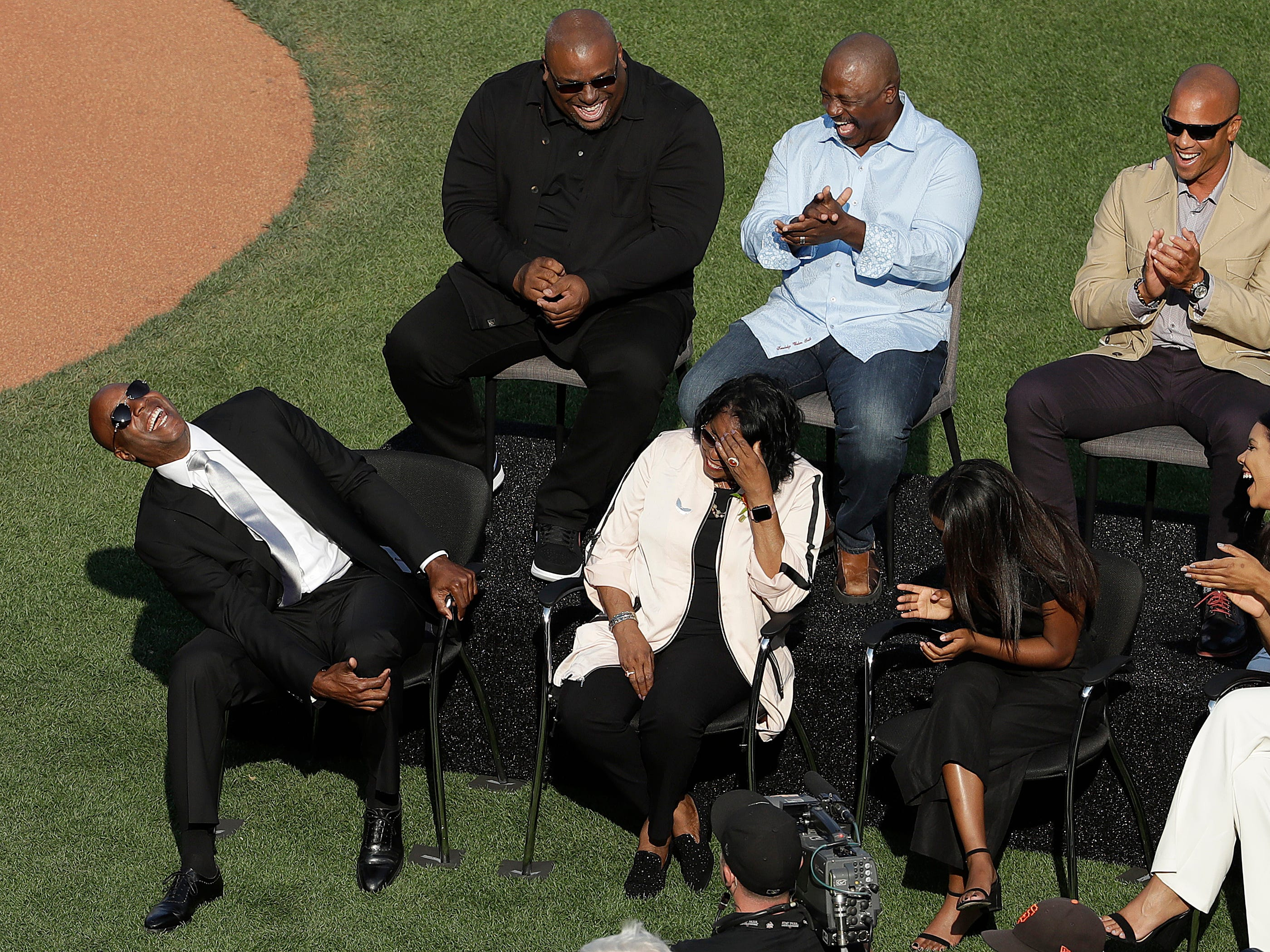 Barry Bonds, left, laughs at a joke told by former manager Dusty Baker during a ceremony held by the San Francisco Giants to retire his No. 25