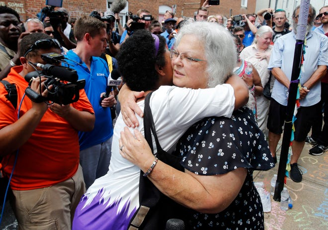 """Susan Bro, mother of Heather Heyer who was killed during last year's Unite the Right rally, embraces supporters after laying flowers at the spot her daughter was killed in Charlottesville, Va., Sunday, Aug. 12, 2018. Bro said there's still """"so much healing to do."""" She said the city and the country have a """"huge racial problem"""" and that if it's not fixed, """"we'll be right back here in no time."""" (AP Photo/Steve Helber) ORG XMIT: VASH111"""