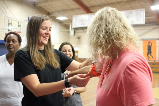 Ruby-Wise Elementary School teacher Angie Sasser practices tightening a tourniquet on the arm of fellow teacher Nina May.