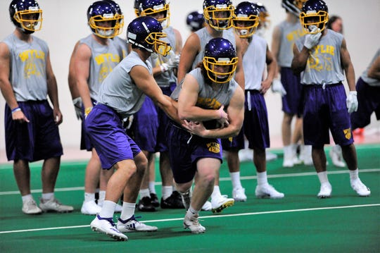 Wylie quarterback Jaxon Hansen hands off to Dax Morris during the first fall practice at the Doghouse on Monday, Aug. 13, 2018.
