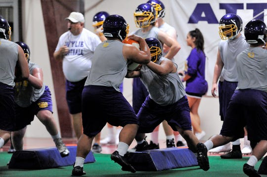 Wylie offensive linemen go through a drill during the first fall practice at the Doghouse on Aug. 18.