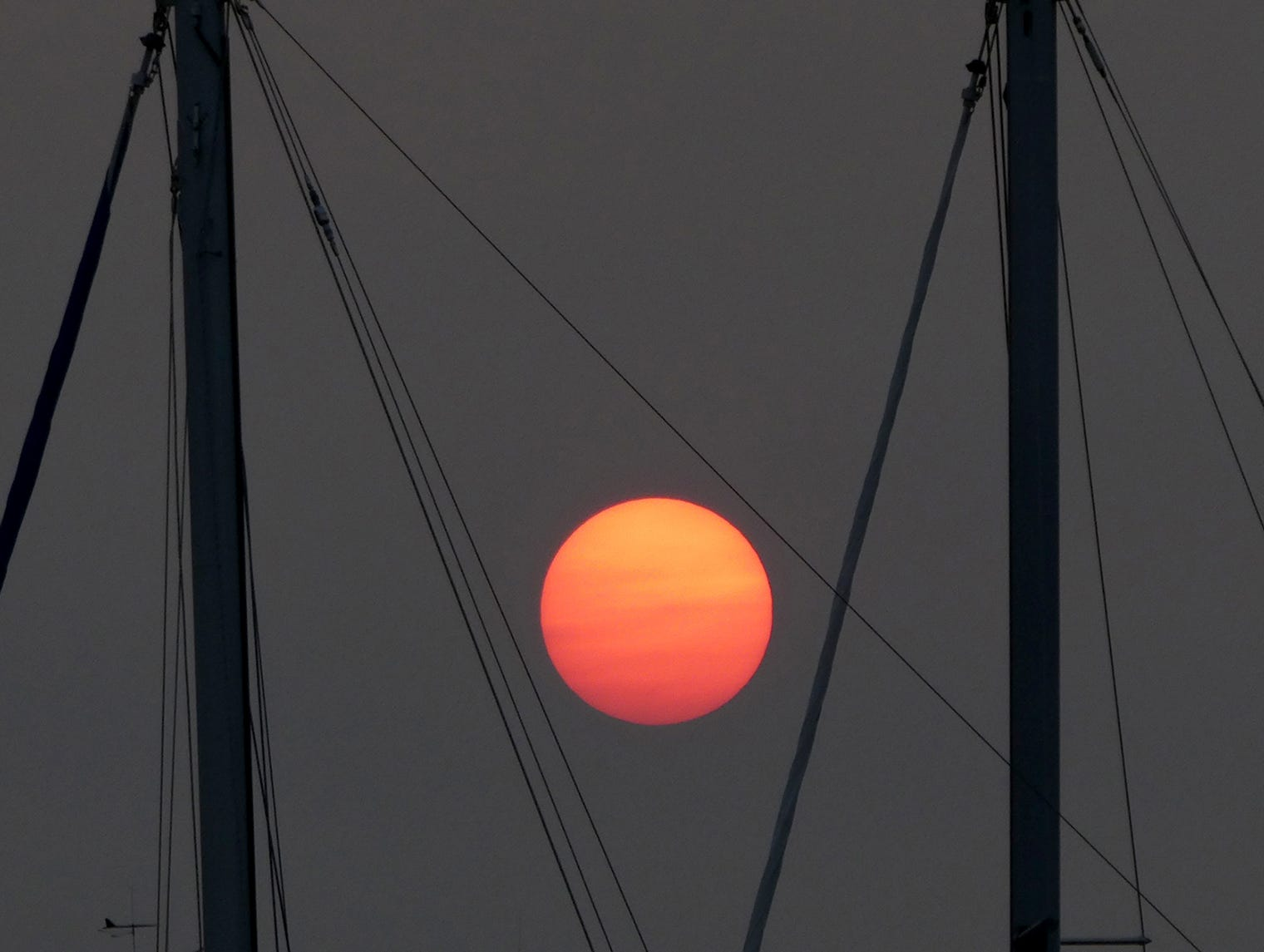 The sun turns orange and red as it sets Sunday August 12. 2018 from he Bremerton Harborside Marina.