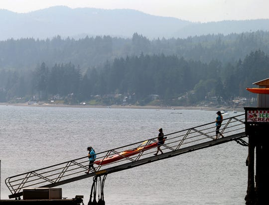 A smoky haze hangs over the Kitsap Peninsula as kayaks from the Olympic Kayak Center at the Silverdale Waterfront Park are taken down to be used on Monday August, 13, 2018.