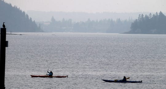 """A smoky haze hangs over the Kitsap Peninsula as a pair of kayakers from the Olympic Kayak Center paddle off Silverdale Waterfront Park on Monday. Air quality is Kitsap is declining and is labeled as """"moderate"""" by the Puget Sound Clean Air Agency. Wildfires in Central Washington and British Columbia are to blame."""