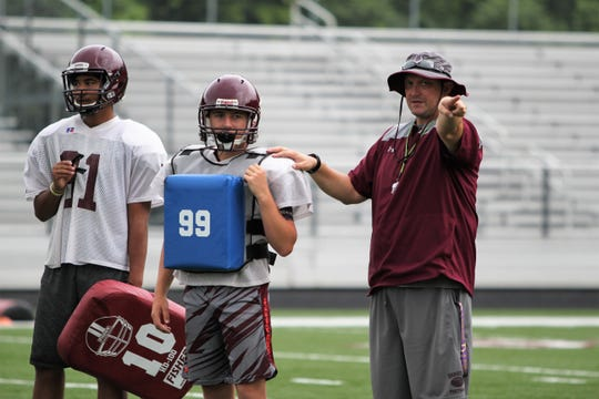 Owen head coach Nathan Padgett, who is entering his fourth season, goes over assignments with a defensive player in practice in preparation for the upcoming season.