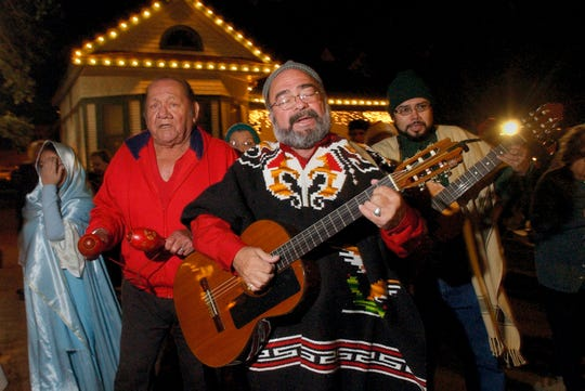 Leo Carrillo, center, leads a group of musicians, including Daniel Gamez, left, and guitarist Joe Miguel Ayala, right, to the next house Saturday, Dec. 15, 2007, as they participate in a Christmas Posada at Heritage Park in Corpus Christi. Carrillo and the choir from Holy Family Catholic Church lead the traditional Mexican celebration as they went from house to house re-enacting Mary and Joseph's journey to find shelter in Bethlehem.