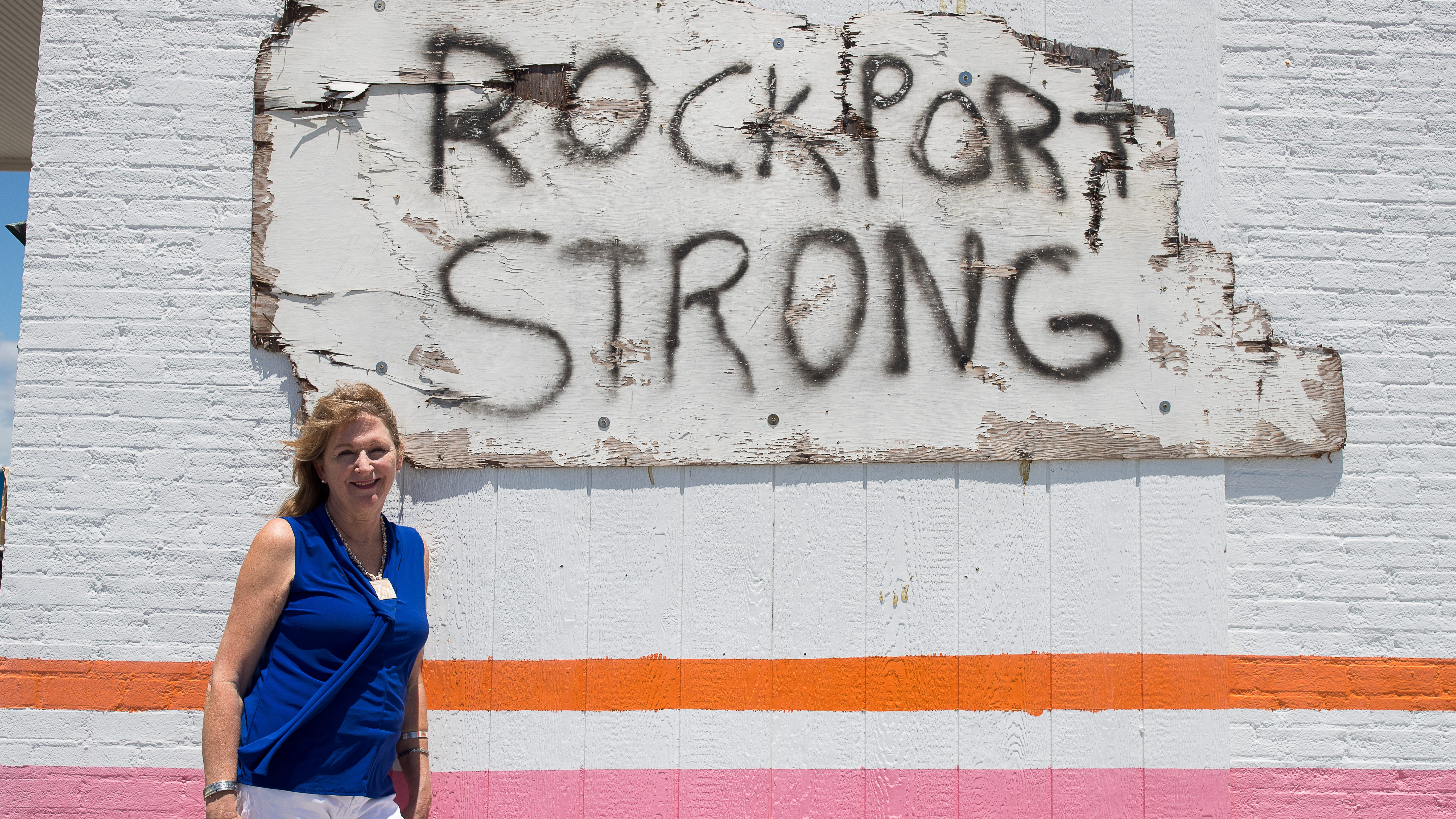 """Jennifer Day, CEO of the Rockport Cultural Arts District, stands in front of a """"Rockport Strong"""" sign hung on the side of a business in downtown Rockport, Texas."""