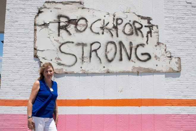 "Jennifer Day, CEO of the Rockport Cultural Arts District, stands in front of a ""Rockport Strong"" sign hung on the side of a business in downtown Rockport, Texas."