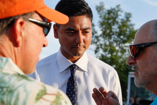 "Hamilton County Clerk of Courts Aftab Pureval speaks with constituents as he campaigns for his 1st House District challenge against veteran Republican Rep. Steve Chabot at a music festival, Friday, June 15, 2018, in Mason, Ohio. The Democratic candidate for Congress in southwest Ohio jokes that besides already going against the electoral odds, he's a ""brown dude with a funny name."" But 35-year-old Aftab Pureval is attracting national attention as tries to unseat veteran Republican Rep. Steve Chabot, part of the Cincinnati-area political landscape for three decades. (AP Photo/John Minchillo)"