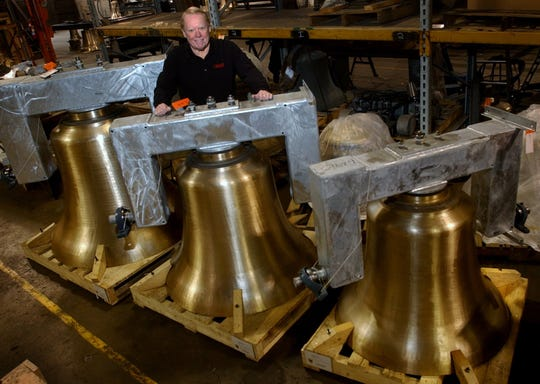 Jim Verdin, president of the Verdin Co. in the East End posed with three bronze bells manufactured by the company. The bells were destined for Christ the King Church in Dallas, Texas. Cincinnati
