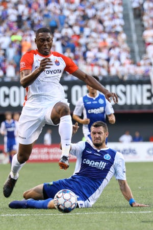 FC Cincinnati's Fanendo Adi leaps over a defender as he rushes for the goal during the club's match vs. Penn FC at Nippert Stadium on Sunday.