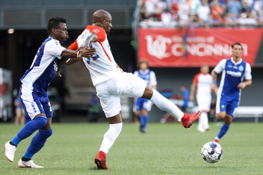 FC Cincinnati's Justin Hoyte is held back as he tries to get to the ball during the club's match vs. Penn FC at Nippert Stadium on Sunday.