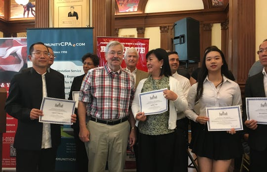 U.S. Ambassador to China Terry Branstad, second from left, poses for pictures after handling out awards at an Immigrant Entrepreneurs Summit on Monday, Aug. 13, 2018, in Des Moines, Iowa.