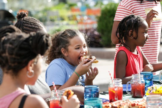 "Nevaeh Justice, 10, of Detroit, sampled the pizza Monday during the filming of an episode of ""Scraps"" at the Quicken Loan Sports Zone at  Cadillac Square. Next to her is Lateefah Carithers, 6, of Detroit."