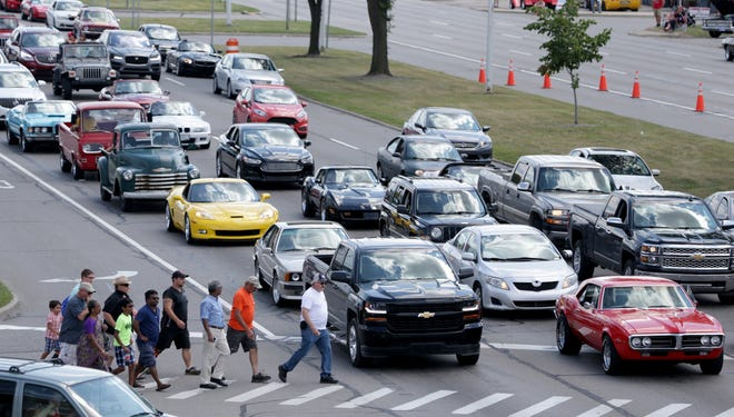 A variety of classic cars mixed in with newer model cars are stopped at a traffic light at Woodward Avenue and Vinsetta as Woodward Dream Cruise fans cross the street during the 2017 Woodward Dream Cruise on Saturday, August 19, 2017.