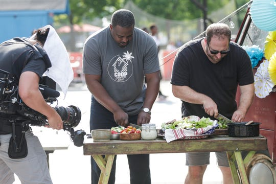 "Detroit chef Maxcel Hardy, center, and ""Scraps"" host Joel Gamoran prepared a meal Monday during the filming of a ""Scraps"" episode at the Quicken Loan Sports Zone at Cadillac Square in downtown Detroit."