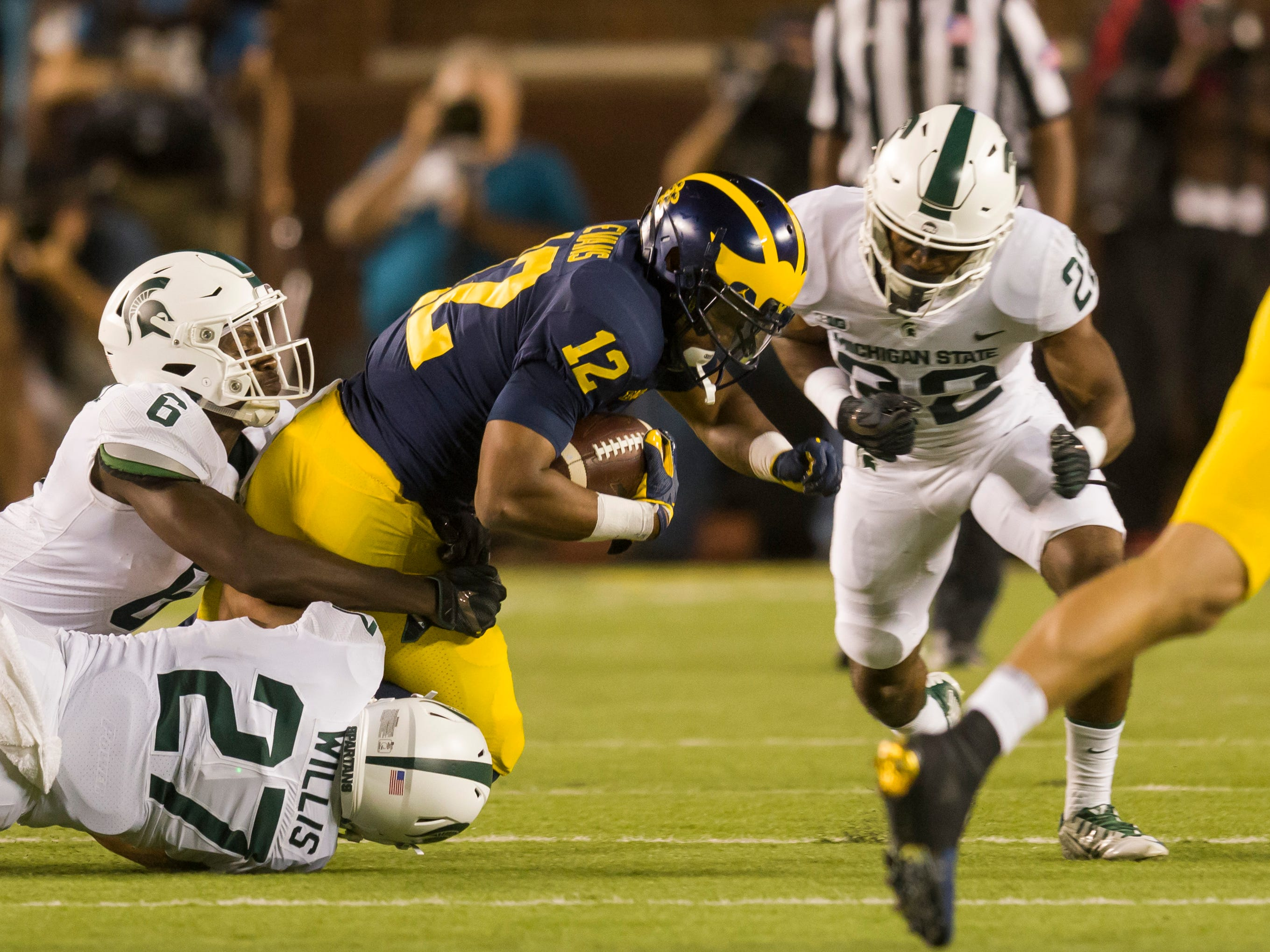 Michigan running back Chris Evans is tackled by Michigan State safety David Dowell (6) and safety Khari Willis (27) in the first quarter of last season's game in Ann Arbor.