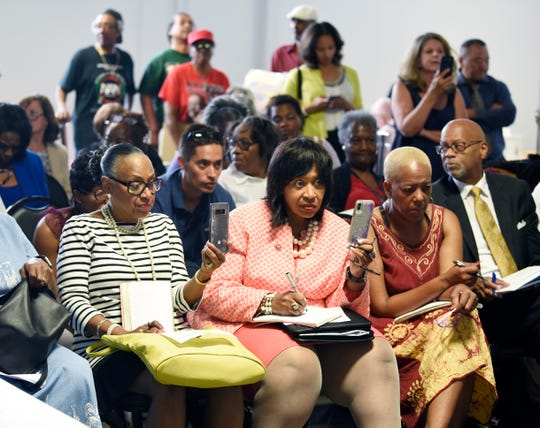 Detroit City Council President Brenda Jones, center, took notes and recorded the meeting.
