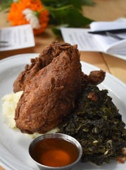 Crispy fried chicken sits atop a pillow of mashed potatoes accompanied by bacon-braised greens.