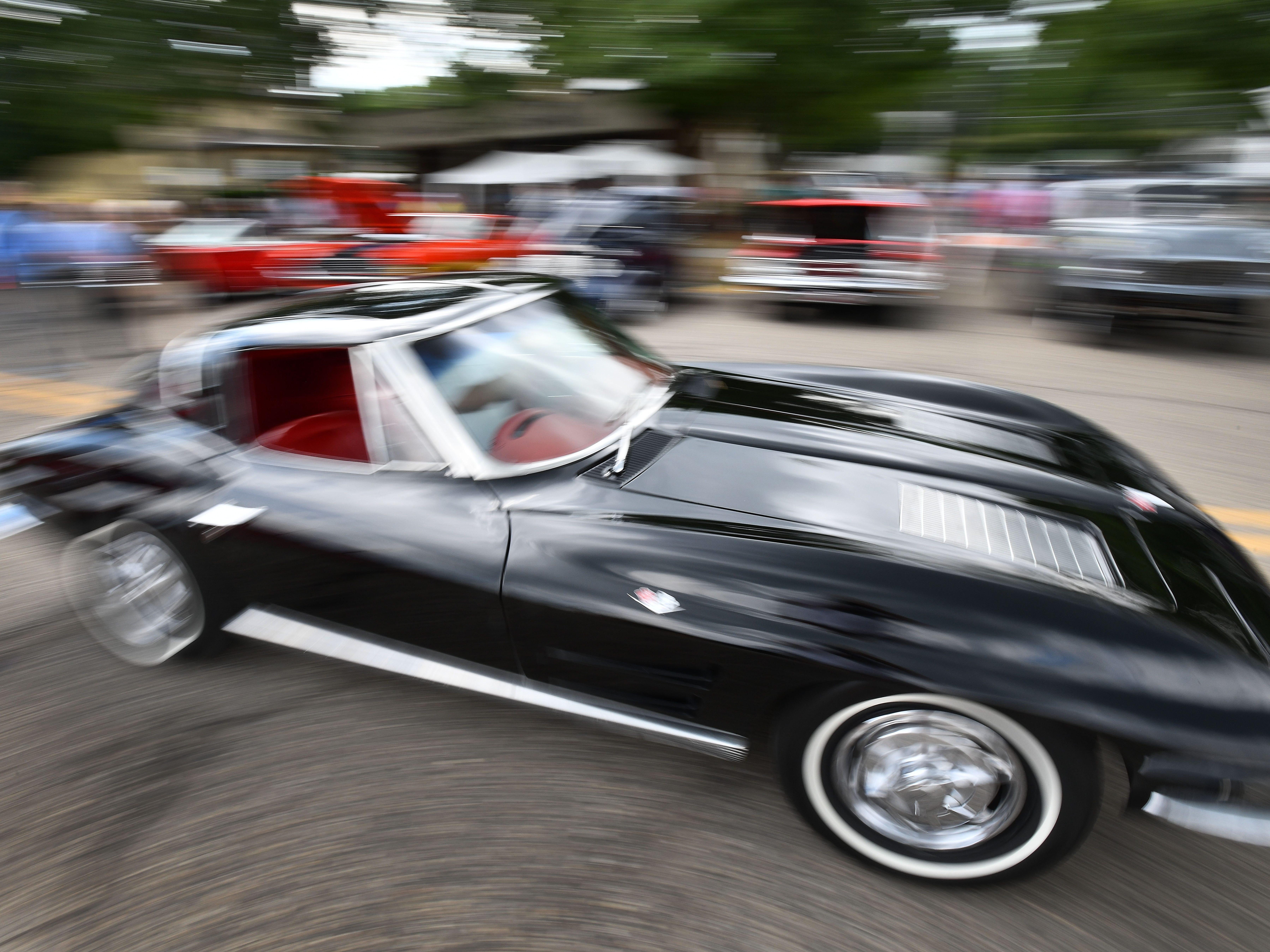 A deep black Corvette cruising through the 19th annual Rockin Rods n' Rochester.