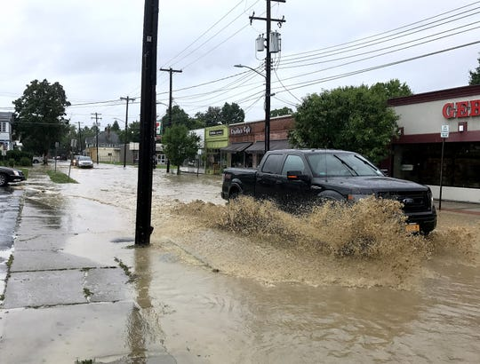 A pickup truck drives through a foot of water on Hoffman Street in Elmira.