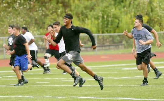 Elmira High School football players run sprints during the opening practice of the season Aug. 13 at Ernie Davis Academy.