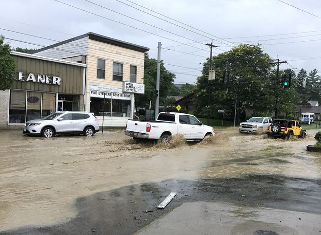 Motorists drive through standing water Monday afternoon at the intersection of West Church and Hoffman streets in Elmira.