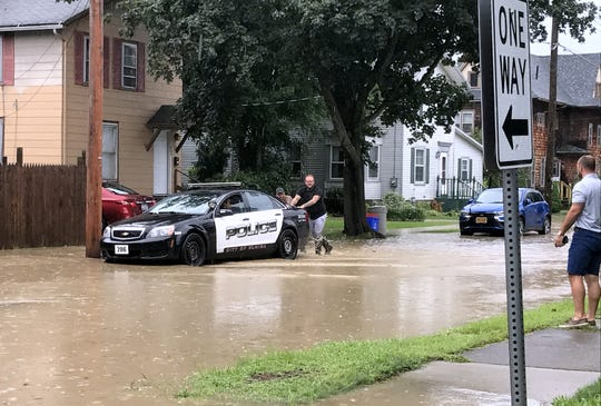 Passersby push a stalled Elmira police cruiser out of standing water Monday on First Street in the city.