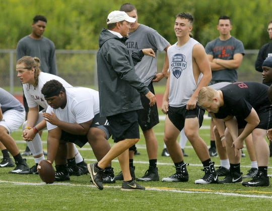 Elmira High School assistant coach Mike Johnston Jr. goes over offense with players during the opening practice of the season Aug. 13 at Ernie Davis Academy.