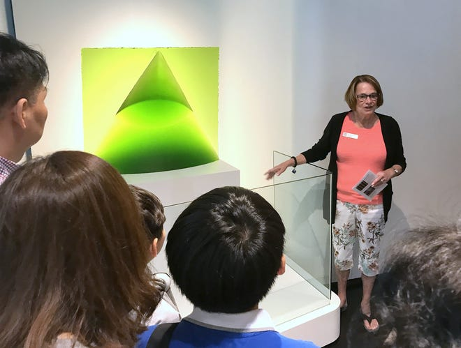 Docent Sandy Mentuck points out information about a display for visitors at the Corning Museum of Glass.