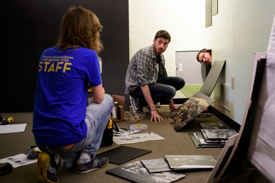 Indiana State Museum employees Jordan Cleland, from left, Jordan Staats and Brian Mancuso, install a new exhibit to highlight the work of archaeologist Glenn Black and philanthropist Eli Lilly inside the Angel Mounds Interactive Center in Evansville, Ind., Monday, Aug. 13, 2018. It will be unveiled on Saturday morning, August 18, for museum visitors.