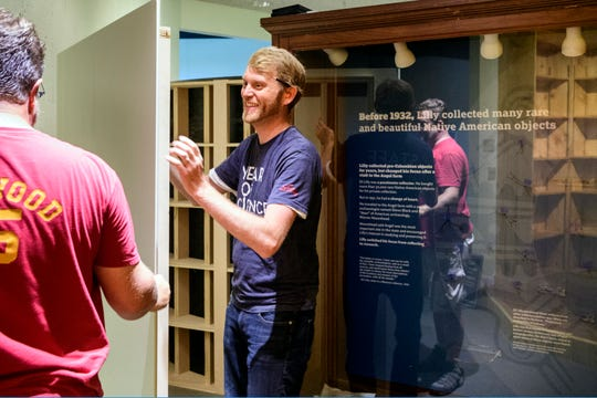 Mike Linderman, left, and John Segner, right, work on installing a wall for the new exhibit highlighting the work of archaeologist Glenn Black and philanthropist Eli Lilly inside the Angel Mounds Interactive Center in Evansville, Ind., Monday, Aug. 13, 2018.