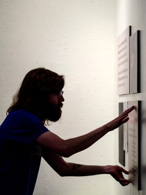 Jordan Cleland, an Indiana State Museum Exhibit Designer, installs panels that explain why archeologist Glenn Black used a magnetometer – a tool used to measure magnetic fields in the ground – during field work inside the Angel Mounds Interactive Center in Evansville, Ind., Monday, Aug. 13, 2018. The new exhibit, which will be unveiled at Angel Mounds on Saturday, highlights the work of Black and philanthropist Eli Lilly in preserving and studying the site of the Native American community near Evansville.