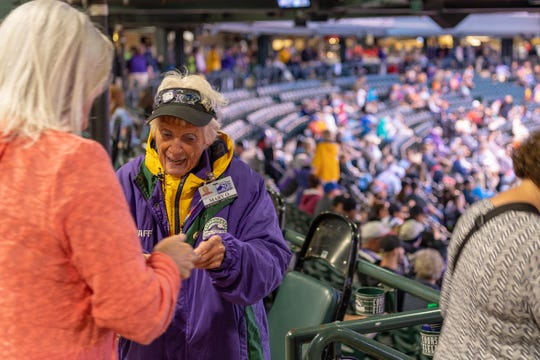 Colorado Rockies usher Mary O'Dell checks a ticket at a recent home game at Coors Field.