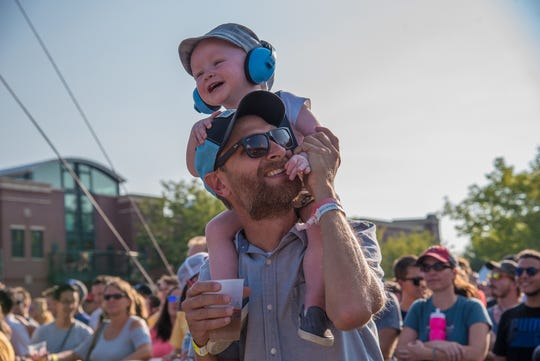 Bryce Merrill carries his son Sebastian Merrill, 1, on his sholders as The Decemberists perform on the Mountain Avenue stage during the final day of Bohemian Nights at NewWestFest on Sunday, August 12, 2018, in Old Town Fort Coolins.