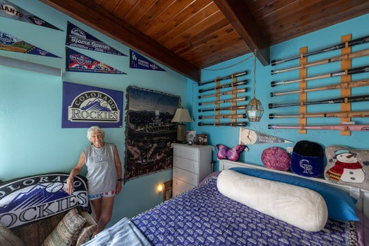 Mary O'Dell, a Fort Collins resident and Colorado Rockies usher for 20 years, poses for a photo in her Horsetooth Reservoir home that sports lots of reminders who her favorite team is.