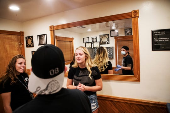 An employee at Pleasures of the Flesh in Fort Myers goes over piercing procedures with a prospective client. In the wake of an arrest at an illegal piercing operation in Lehigh Acres Friday, the shop's owner said such operations can cause their customers problems.