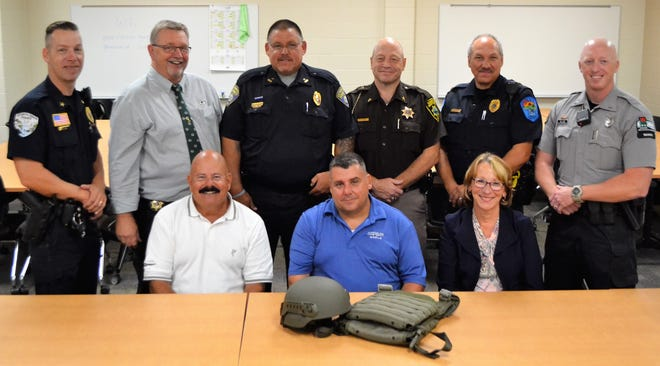 Several members of the Oconto County Law Enforcement Executive Group stand with a few of the donors that made purchase of ballastic vests and helmets, a set of which is on the table, for 50 officers in Oconto County possible. From left, front: Stu Winarski, owner of Chrysler World, Abrams, Jerry Parham, fleet manager at Chrysler World, and representing the Bond Foundation, Beth Larson; back row: Oconto Falls Police Chief Brad Olsen, Oconto County Sheriff Mike Jansen, Oconto Police Chief Mike Rehberg, Oconto County Chief Deputy Ed Janke, Suring Police Chief Phil Christenson, and DNR warden supervisor Andy Lundin.