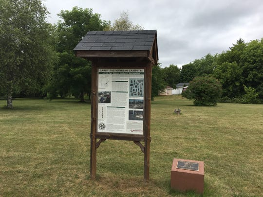 The kiosk describing the Cardy Paleo-Indian Campsite in Sturgeon Bay, along with a stone marker for the site.