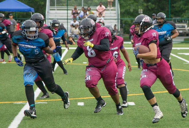 S.C. Smash's Christina Davis, right, carries as Rosalyn Martin (8) blocks for her during the game against the Savannah Hurricanez in Savannah, GA. The Smash will travel hundreds of miles to face other teams in the Women's Football Alliance.