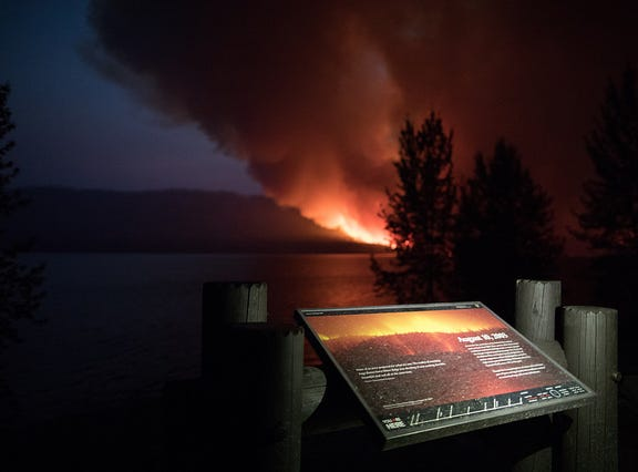The Howe Ridge fire burns Sunday evening lighting up an interpretive sign explaining a previous fire in the area.