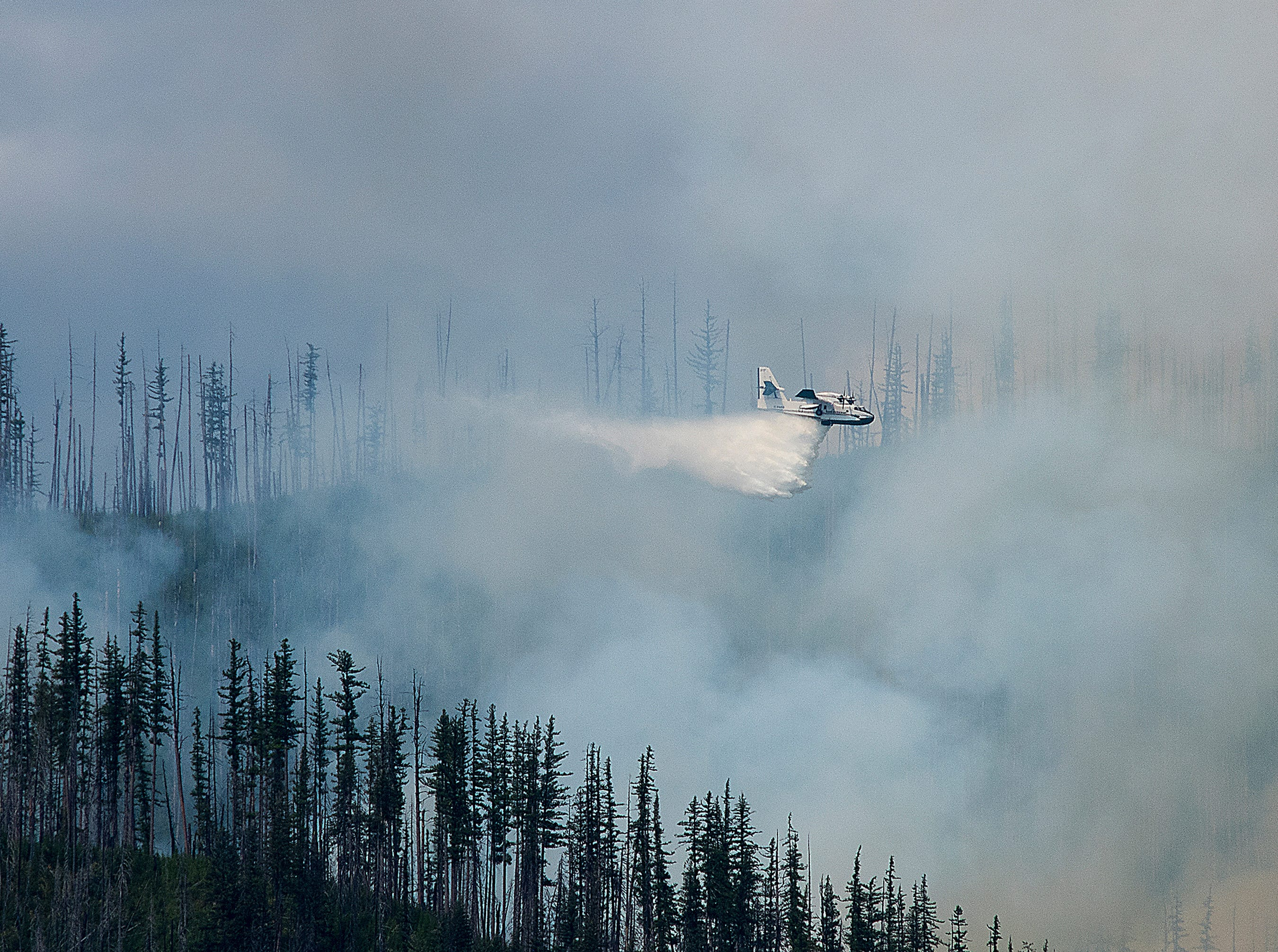 In this photo taken Sunday, Aug. 12, 2018, an air tanker drops water over a wildfire burning in Glacier National Park, Mont. The fire was started by lightning on Saturday night and forced the evacuation of the Lake McDonald Lodge and closed part of the scenic Going-to-the-Sun Road in the park.