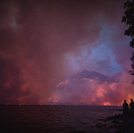 Visitors watch the Howe Ridge fire Sunday evening as it blows up in erratic winds and dry fuels.