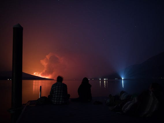 Two people watch the Howe Ridge fire as it burns Sunday evening near Lake McDonald.