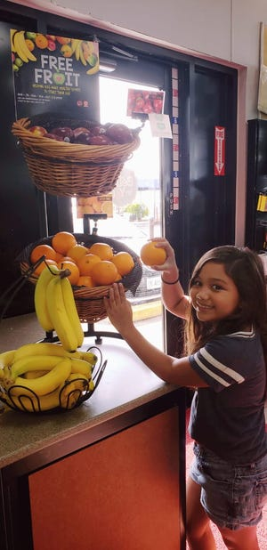 School student Sophie Franquez reaches reaches for an orange  provided by Circle K's Free Fruit for Kids program.