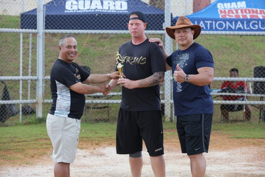 Navy's Mike Cahill, center, receives the first place trophy for the 2018 Armed Services Softball Tournament home run derby.