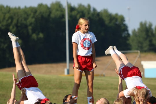 Lilly O'Daniel stands in the middle of a pyramid being built as the cheerleaders perform.
