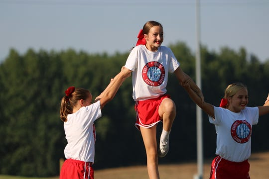 Lauren Hendrickson stands on top of the cheer pyramid.
